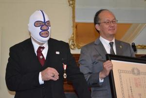 3日、米ニューヨーク州バファローで行われた叙勲伝達式で、在ニューヨーク総領事館の高橋礼一郎総領事から賞状を贈られた覆面姿のデストロイヤーさん(共同)