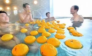 香りを楽しみながらゆず湯につかる入浴客=21日、福井市の鷹巣荘