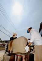 厳しい暑さの中、豪雨被害の片付けをする人たち=18日午前、岡山県倉敷市真備町地区