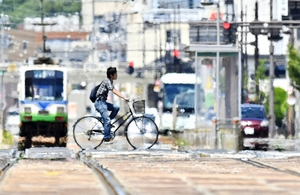 揺らめくかげろうの中を移動する人=7月29日午後0時半ごろ、福井県福井市のフェニックス通り