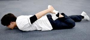 太もも筋肉チェック(2) 両足を閉じたまま、うつぶせで片足ずつ折り曲げ、太ももの表側の硬さを確かめる。