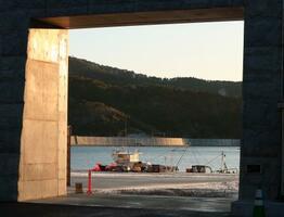 朝日を浴びる防潮堤と漁船=2月27日、宮城県石巻市