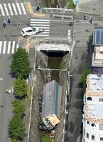 乗用車に衝突するなどし、道路脇の川に転落したトラック=3日午前9時51分、神戸市灘区(共同通信社ヘリから)