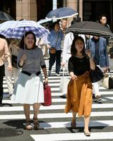 今年初めて真夏日を観測した東京都心部。銀座では日傘を差して歩く女性の姿が目立った=24日午後