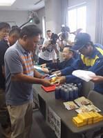 避難者は健康チェックに回答し、支援物資を受けとる。別のバスで到着した高浜町議も手順を確認している様子。