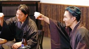 オンライン飲み会イベントで杯を掲げる橘ケンチさん(右)=東京都内
