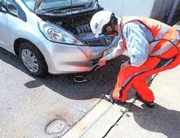 鏡のついた工具で車両下回りの点検をするJAF福井支部の職員(同支部提供)