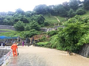 斜面から濁った水が路上に流れ込む現場=7月7日、福井県福井市内