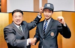 熊野輝光担当スカウト(左)から帽子をかぶせてもらい笑顔を見せる牧丈一郎=13日、京都市内のホテル