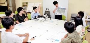 給水システムの設置工程などを確認する、図面を手にした笠井利浩教授(中央)や学生ら=3日、福井市の福井工業大学