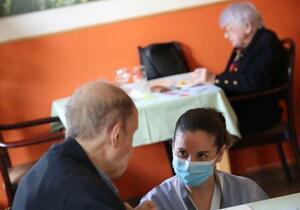 ブリュッセルの高齢者向け住宅で、マスクを着けて入居者の世話をする従業員=26日(ロイター=共同)