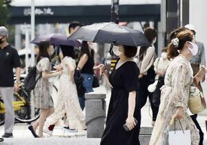 猛暑日となった名古屋市で日傘にマスクをして歩く女性=9日午後
