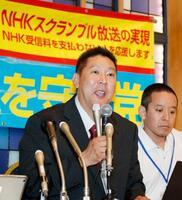 比例代表で当選が決まり、笑顔で記者会見する政治団体「NHKから国民を守る党」の立花孝志代表(左)=22日午前4時31分、東京・赤坂