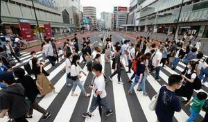 東京・新宿を行き交うマスク姿の人たち。国内で確認された新型コロナウイルスの感染者数が累計で2万人を超えた=4日午後