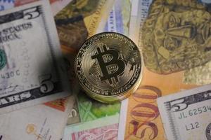 紙幣の上に置かれた仮想通貨「ビットコイン」のマーク(ゲッティ=共同)