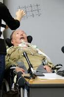 記者会見で文字盤を使って訴えるALS患者の増田英明さん=5日午後、京都府庁