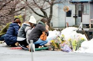 献花台の前で手を合わせ、田中蓮ちゃんに哀悼の意をささげる親子連れら=21日、福井県越前市上太田町