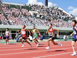 日本人初の100メートル9秒台が樹立されたコースで快走する児童たち=14日、福井市の県営陸上競技場