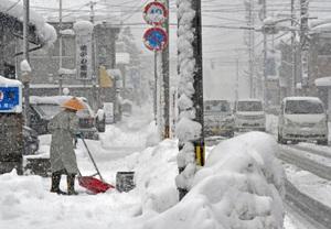 雪が降りしきる中、除雪作業する市民ら=福井県大野市