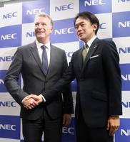 記者会見で握手するNECの藤川修執行役員(右)とトランスジーンのエリック・ケメナー最高科学責任者=27日、東京都千代田区