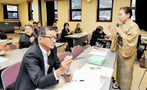 正しい箸の使い方の指導方法を解説する山口ちとせさん(右)=福井県鯖江市民活動交流センター