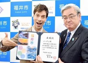 「福井市のPRは任せて」と観光大使の委嘱状を手にするパックン(左)=13日、東京都千代田区の市東京事務所