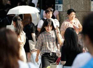 梅雨明けしたとみられる名古屋市で、日差しをうちわで遮りながら歩く女性=28日午後
