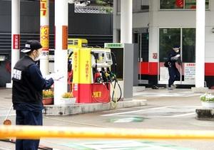 強盗事件が起きたガソリンスタンドを調べる捜査員。建物(右奥)の2階が被害に遭った事務所=5月4日午前7時20分ごろ、福井県福井市大宮2丁目