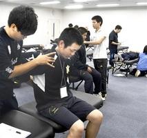 理学療法士らの指導で肩や肘の可動域の確認をする高校生投手たち=福井県福井市の福井総合病院