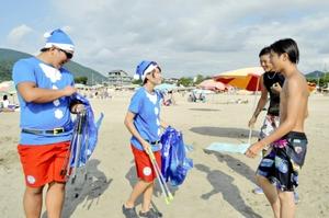 海水浴客らにごみ拾いを手伝ってもらうサンタクロース姿のライフセーバーたち=18日、福井県高浜町和田の若狭和田海水浴場