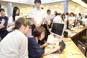 マイナンバーカードを使った本の貸し出し手順を学ぶ市町職員ら=9月10日、福井県の福井市立みどり図書館