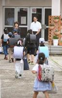 授業が再開され、登校する大阪府高槻市立寿永小の児童ら=21日午前
