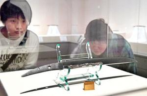 短刀に施された精巧な透かし彫りに見入る来場者=24日、福井市立郷土歴史博物館