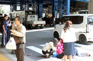 市営バス(左奥)が横断歩道を渡っていた歩行者をはねた現場=21日午後、神戸市