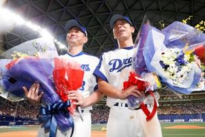 現役最後の一戦を終え、花束を手にする中日の岩瀬仁紀投手(左)と荒木雅博内野手=13日、ナゴヤドーム