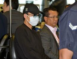 帰国のため空港に到着したバドミントン男子の桃田賢斗選手(手前)=15日、クアラルンプール近郊(共同)