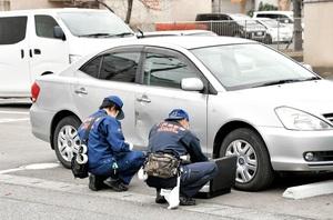 福井大附属義務教育学校西側の駐車場に乗り捨てられた車を調べる捜査員=11月28日午後2時10分ごろ、福井県福井市二の宮4丁目