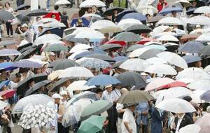 雨の中、街頭演説を聞く有権者=13日、横浜市