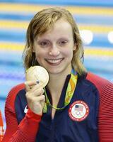 リオデジャネイロ五輪の競泳女子800メートル自由形で優勝し、金メダルを手に笑顔のケイティ・レデッキーさん(共同)