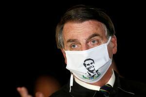 報道陣の取材に応えるブラジルのボルソナロ大統領=22日、ブラジリア(ロイター=)