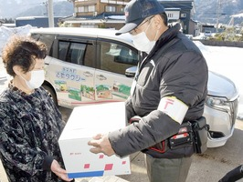 ゆうパックの配送に当たる近助タクシーのドライバー(右)=2月1日、福井県永平寺町吉波