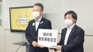 「福井県緊急事態宣言」と書かれたボードを持つ杉本達治知事(左)=6月24日、福井県庁