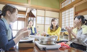宇野いく子さん(右)と山野草の天ぷらなどを味わう参加者=2019年6月、福井県池田町