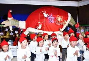 サンタ姿の恐竜の前で歌を披露する子どもたち=1日、福井県勝山市の県立恐竜博物館