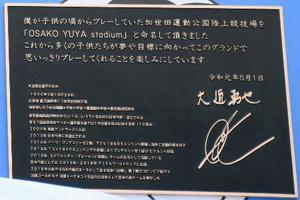 スタジアムの看板の土台にあしらわれた大迫勇也選手が寄せたメッセージ=16日、鹿児島県南さつま市