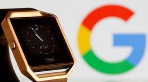 フィットビットの腕時計型ウエアラブル端末とグーグルのロゴ=2019年11月(ロイター=共同)