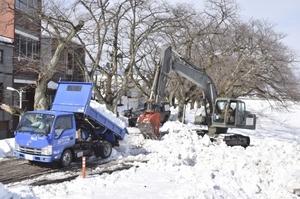 排雪作業を行う陸上自衛隊の油圧ショベル=16日午前10時35分ごろ、福井市の足羽川九十九橋南詰