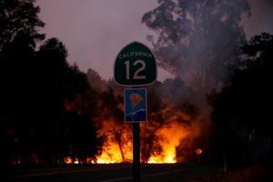 カリフォルニアの山火事の現場と、州道の標識=10日(ゲッティ=共同)
