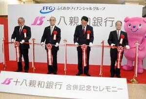 「十八親和銀行」の誕生を記念する式典に参加した森拓二郎初代頭取(左端)と吉沢俊介会長(右端)。中央左は中村法道長崎県知事、同右はふくおかFGの柴戸隆成社長=1日午前、長崎市