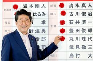 自民党本部の開票センターで、当確者の名前にバラを付ける安倍首相=21日午後9時47分、東京・永田町